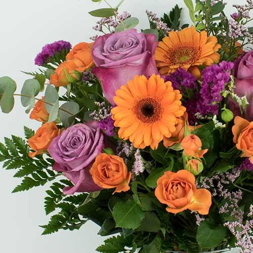 Ramo con gerberas naranjas y rosas moradas
